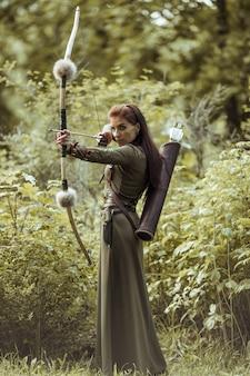 Portret van een vrouw in een middeleeuws kostuum. vrouw krijger jacht. houd de boog in je handen.