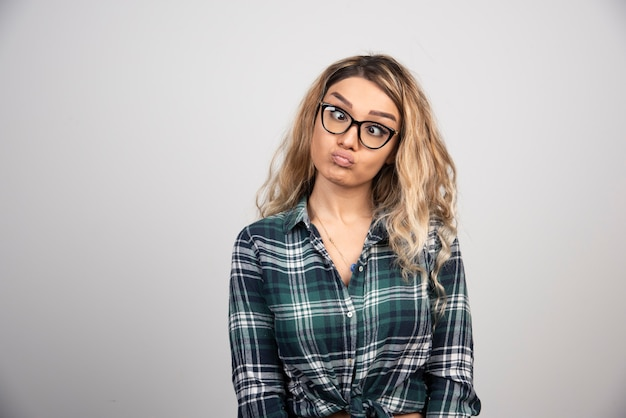 Portret van een vrouw in een modieuze bril die een dwaas gezicht maakt.