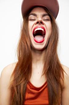 Portret van een vrouw in een pet mond wijd open model ogen gesloten aantrekkelijke look geïsoleerde achtergrond