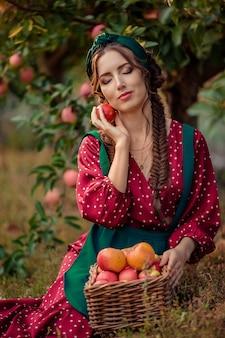 Portret van een vrouw in een rode jurk die in de buurt van rieten manden met rijpe appels zit en een appel in haar handen houdt, haar ogen sluit. oogsten in de appelboomgaard
