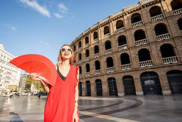 Portret van een vrouw in een rode jurk met een spaanse handventilator die voor het amfitheater van de arena in de stad valencia, spanje staat