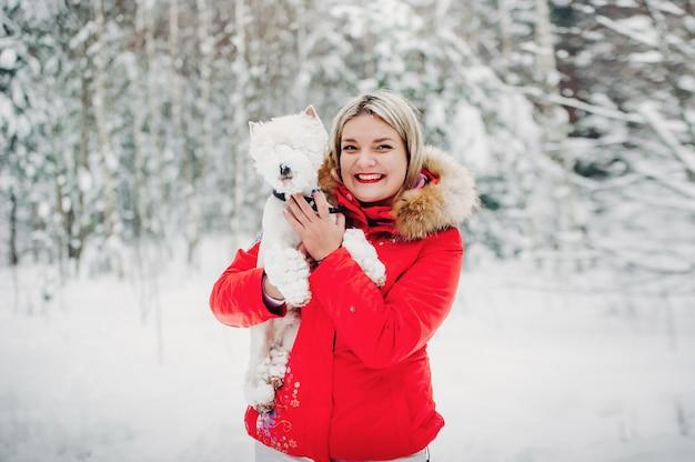 Portret van een vrouw in een rood jasje met een hond in een koud winterbos.