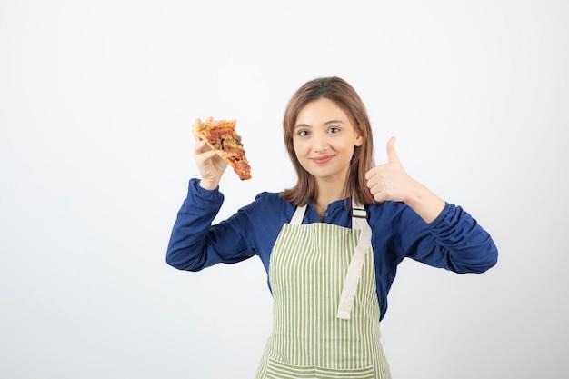 Portret van een vrouw in een schort die een stuk pizza op wit toont