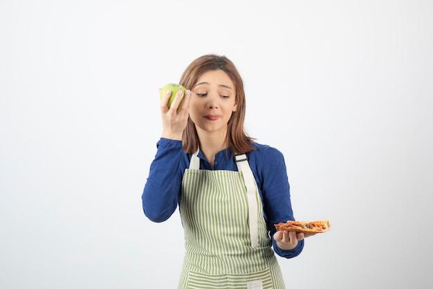 Portret van een vrouw in een schort die probeert te kiezen wat ze appel of pizza gaat eten