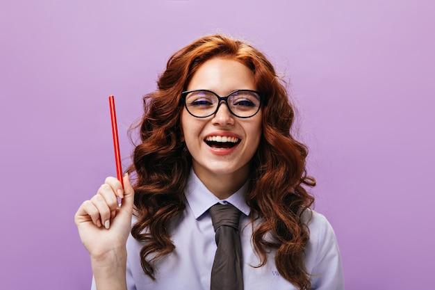 Portret van een vrouw in een shirt die lacht en rood potlood vasthoudt