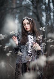 Portret van een vrouw in een sprookjebeeld van een donkere koningin in een mysterieus bos