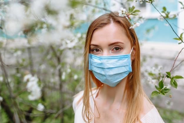 Portret van een vrouw in een wit jasje en een medisch masker, staande in een kersenbloesem