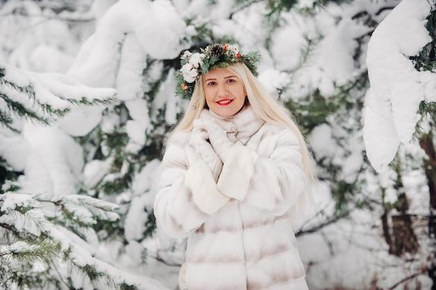 Portret van een vrouw in een witte bontjas in een koude winterbos.