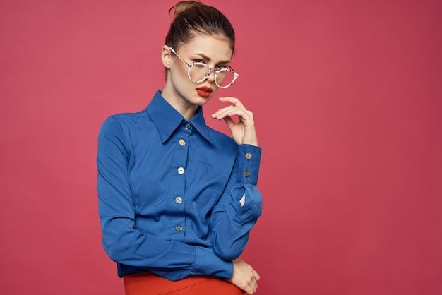 Portret van een vrouw in glazen en in een blauw overhemd rood lippen roze