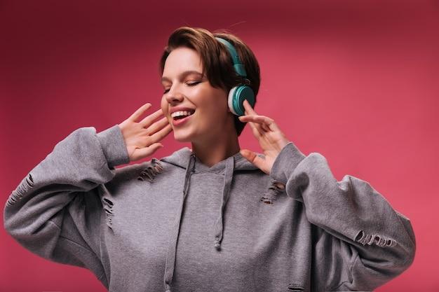 Portret van een vrouw in grijze hoodie, luisteren naar muziek in de koptelefoon. charmante donkerharige dame in goed humeur vormt en geniet van liedjes op roze achtergrond