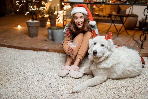Portret van een vrouw in kerstmuts met haar schattige hond die een nieuwjaarsvakantie viert, samen zittend op het prachtig versierde terras thuis