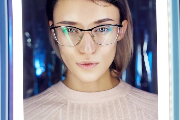 Portret van een vrouw in neon gekleurde reflectieglazen