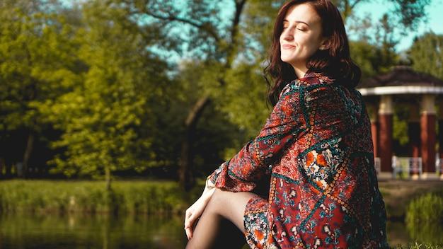 Portret van een vrouw in profiel rustend op de natuur in de buurt van de rivier. zonnige sudderdag