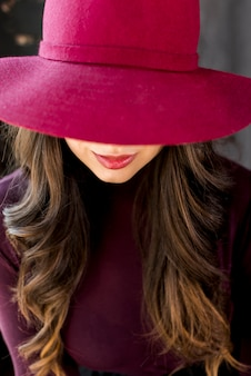 Portret van een vrouw in roze hoed die haar ogen behandelt