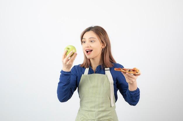 Portret van een vrouw in schort die appel kiest om boven pizza te eten