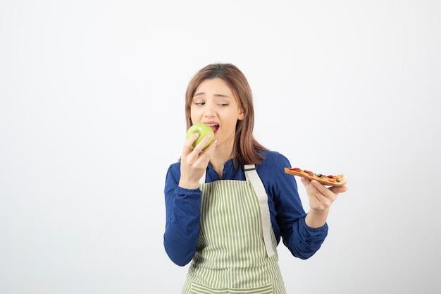 Portret van een vrouw in schort die groene appel eet terwijl ze naar pizza kijkt
