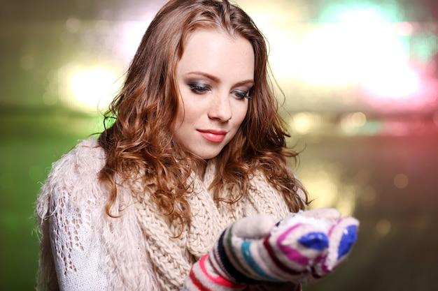 Portret van een vrouw in sjaal en handschoenen op lichte achtergrond