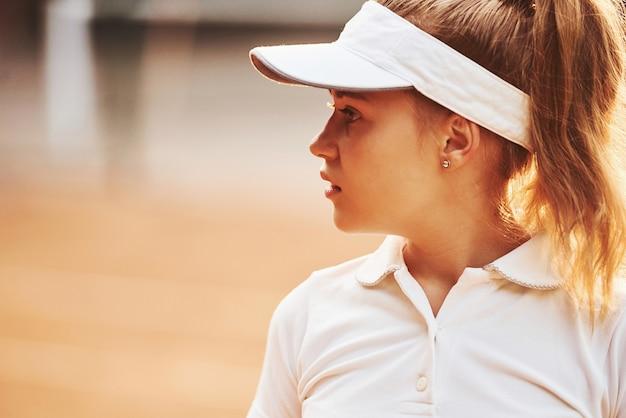 Portret van een vrouw in sportieve tenniskleding buitenshuis.