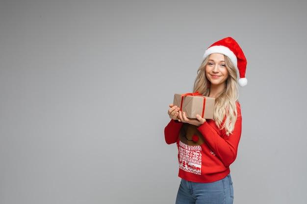Portret van een vrouw in trui en kerstmuts houdt een doos met een cadeautje vast