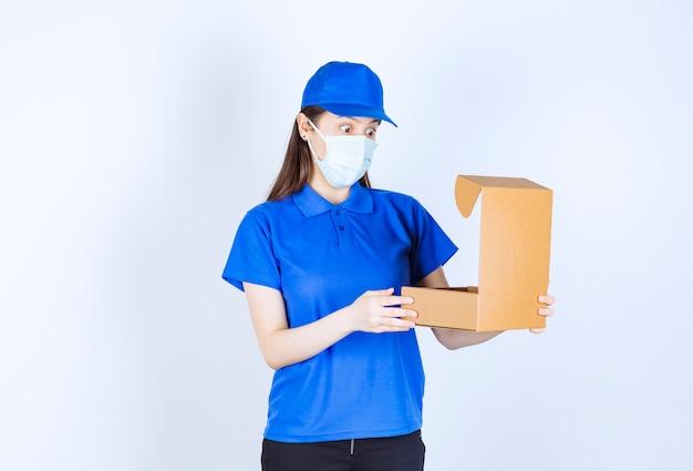 Portret van een vrouw in uniform en medisch masker die een papieren doos opent