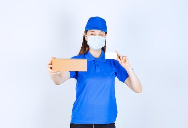 Portret van een vrouw in uniform en medisch masker met papieren doos