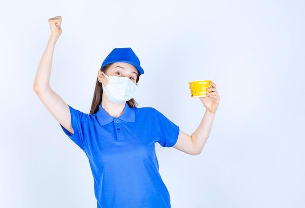 Portret van een vrouw in uniform en medisch masker met plastic beker