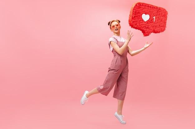 Portret van een vrouw in zonnebril en roze outfit als teken te houden en camera te kijken met perplexiteit.