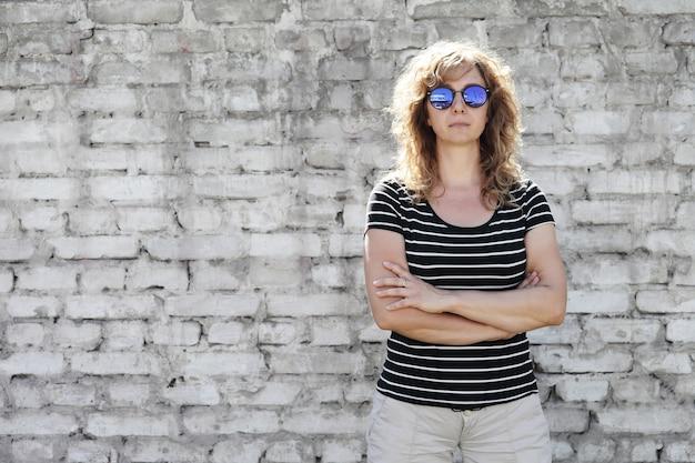 Portret van een vrouw in zonnebril op de achtergrond van een lichte bakstenen muur