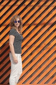 Portret van een vrouw in zonnebril tegen de achtergrond van een oranje gestreepte muur