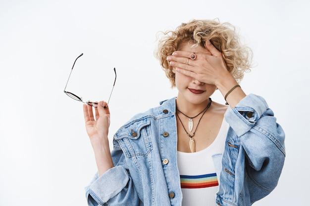 Portret van een vrouw kan niet kijken naar een grof ding dat een bril afdoet die frames in de hand houdt als het zicht bedekken met de handpalm en glimlachend wacht op de tijd om de ogen over de witte muur te openen