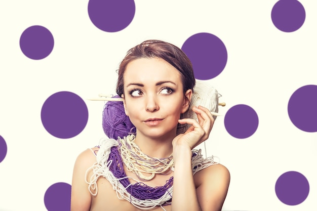 Portret van een vrouw met ballen van wol en breinaalden in haar haar op witte achtergrond