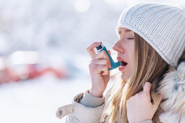 Portret van een vrouw met behulp van een astma-inhalator in een koude winter
