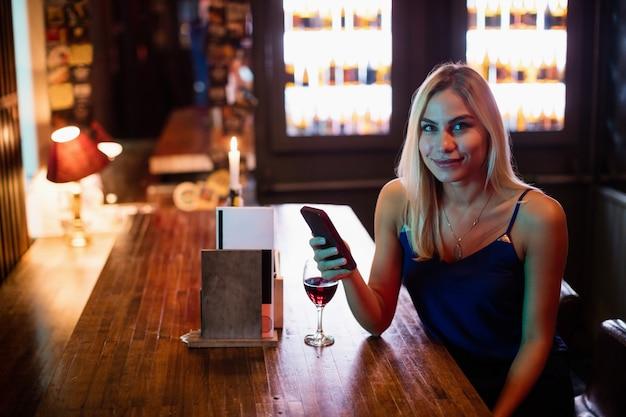 Portret van een vrouw met behulp van mobiele telefoon met rode wijn op tafel
