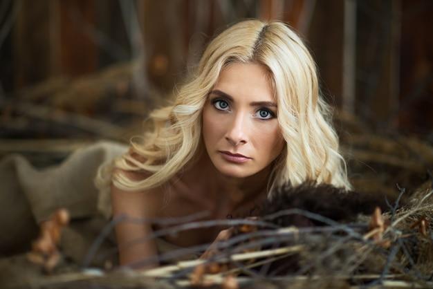 Portret van een vrouw met blond haar en grote groene ogen die dichtbij boomtakken liggen en camera bekijken