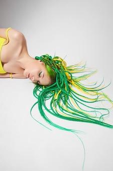 Portret van een vrouw met creatief gekleurd haar in groene en gele kleur
