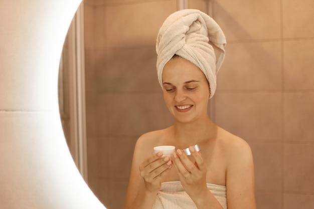Portret van een vrouw met crème in handen, weerspiegeling van een lachende vrouw met een handdoek op haar hoofd die schoonheidsprocedures thuis in de badkamer doet, voor haar huid zorgt.