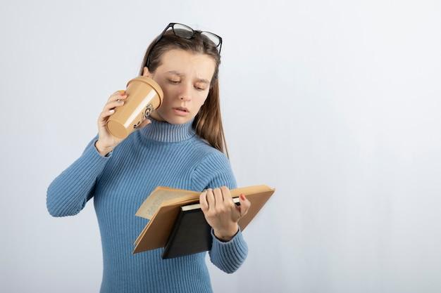 Portret van een vrouw met een bril die een boek leest met een kopje koffie.