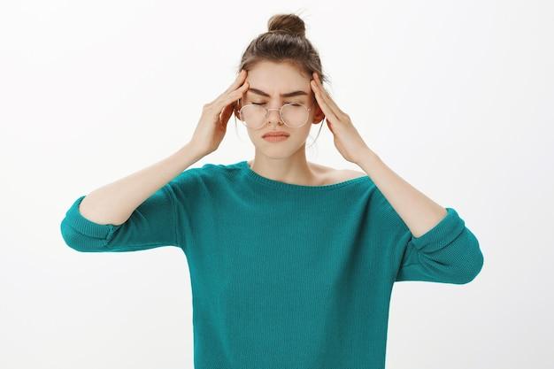Portret van een vrouw met een bril met hoofdpijn, duizeligheid of koorts, migraine