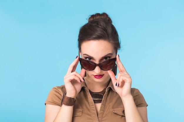 Portret van een vrouw met een bril op een blauwe muur.