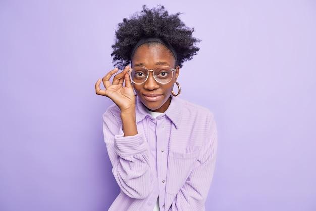 Portret van een vrouw met een donkere huidskleur kijkt aandachtig door een bril