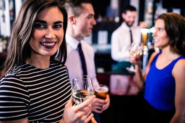 Portret van een vrouw met een drankje met vrienden in een bar