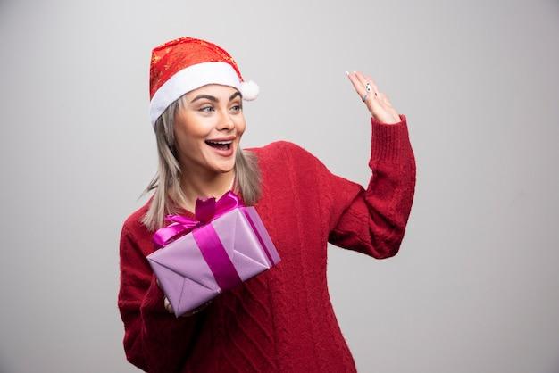 Portret van een vrouw met een geschenkdoos die iemand begroet.