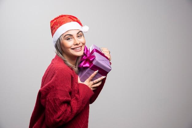 Portret van een vrouw met een geschenkdoos die lacht op een grijze achtergrond.