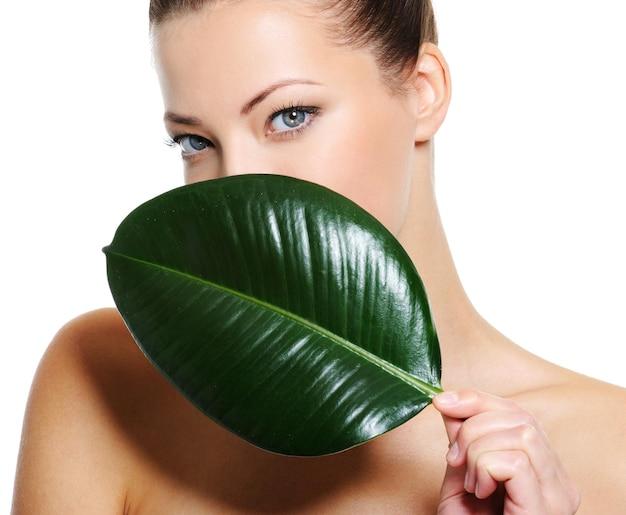 Portret van een vrouw met een gezonde huid die haar gezicht behandelt door vers groot blad
