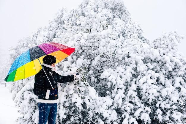 Portret van een vrouw met een kleurrijke paraplu die een sneeuwboom raakt