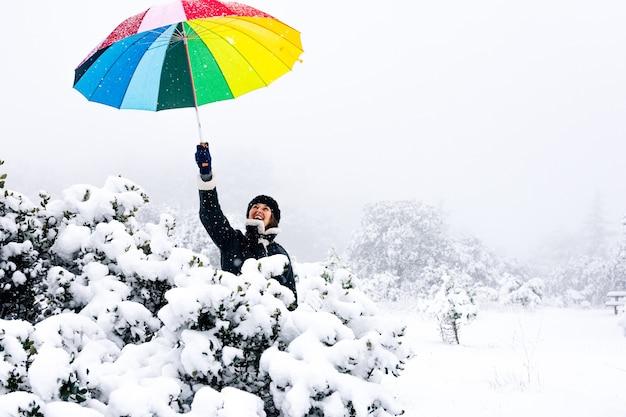Portret van een vrouw met een kleurrijke paraplu tijdens een sneeuwval.