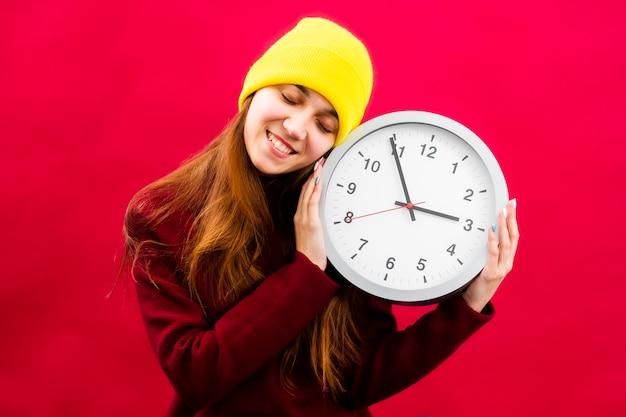 Portret van een vrouw met een klok op een rode achtergrond