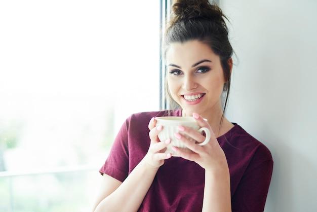 Portret van een vrouw met een kopje koffie in de ochtend