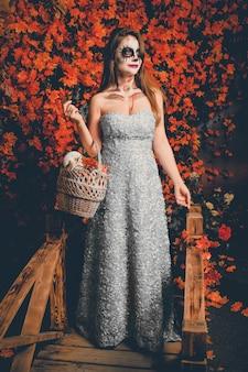 Portret van een vrouw met een make-up van een geest en in een lange jurk met een mand vast.