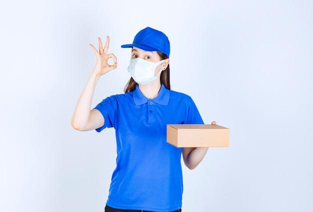 Portret van een vrouw met een medisch masker met een papieren doos die een goed gebaar toont